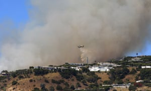A helicopter makes a water drop as flames threaten homes in the Pacific Palisades area of Los Angeles on Monday.