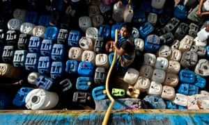 A woman fills water containers from a tanker in New Delhi.