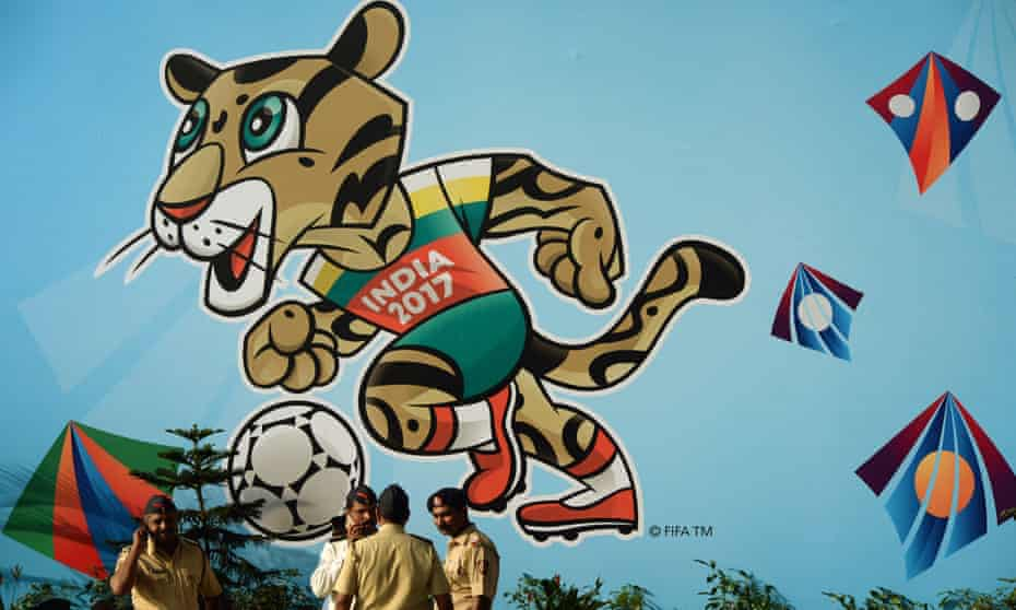Indian policemen stand near a poster of the Under-17 World Cup mascot
