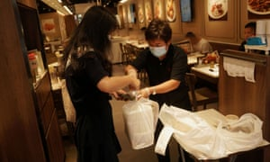 A staff member hands takeaway food to a customer at a restaurant in Hong Kong.