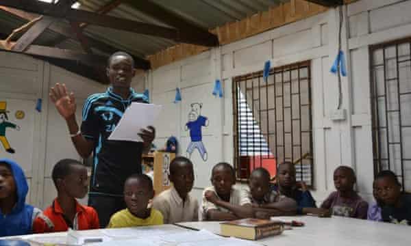 Samson Otieno, aged 22, teaching young boys in Kibera