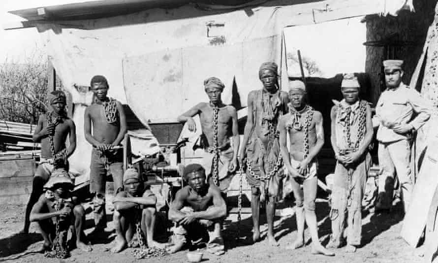 A soldier, probably German, supervising Namibian war prisoners some time between 1904 and 1908