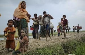 Rohingya families make their way through muddy water after crossing the Bangladesh-Myanmar border.