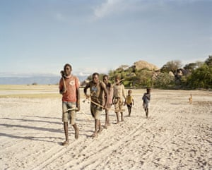 In the morning, a group of young Hadza boys leave the camp to hunt for meat and honey