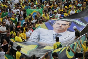 Supporters display a giant banner with the likeness of Brazil's new president, Jair Bolsonaro, during his inauguration in Brasilia, Brazil