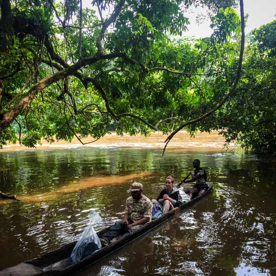 Horeb (L) and Lisa cross the Epulu River on the way to the Bapela outpost inside of the Okapi wildlife reserve, Democratic Republic of Congo