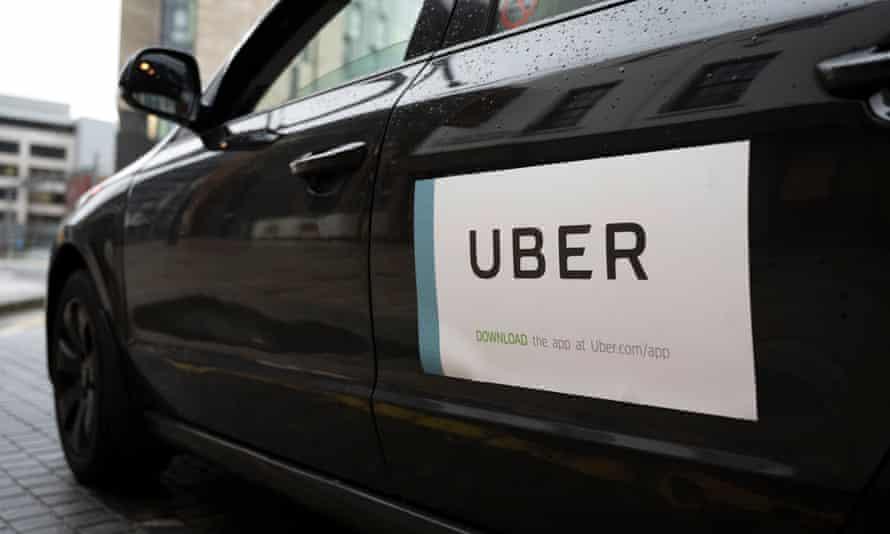 Uber sign on side of shiny black car