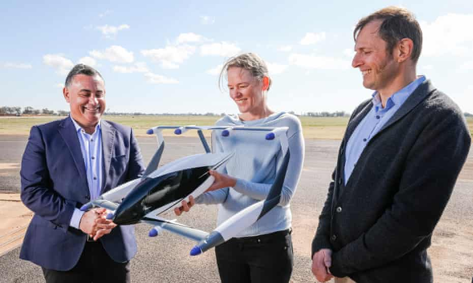 two men in suits and a woman in a jumper hold a model of the electric aircraft