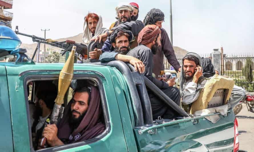 Taliban fighters ride through Kabul in a pickup truck