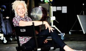 Ellen Von Unwerth sitting sideways on a director's chair smiling broadly
