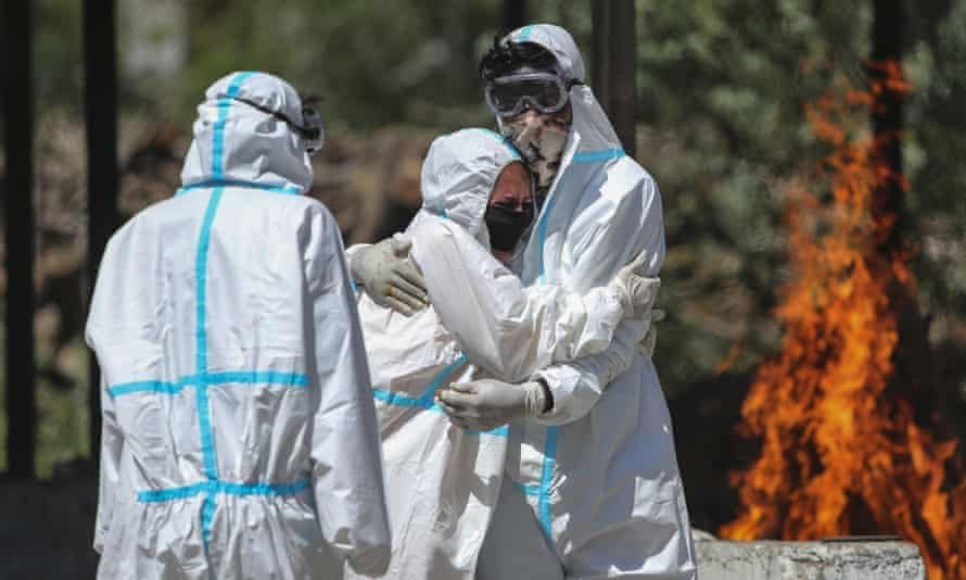 Two people in white hazmat suits hug in front of a funeral pyre, as a third looks on