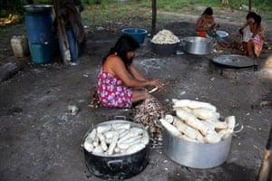 Une mère prépare la nourriture de ses enfants dans le village de Kamayura, dans le parc national de Xingu. Brésil.