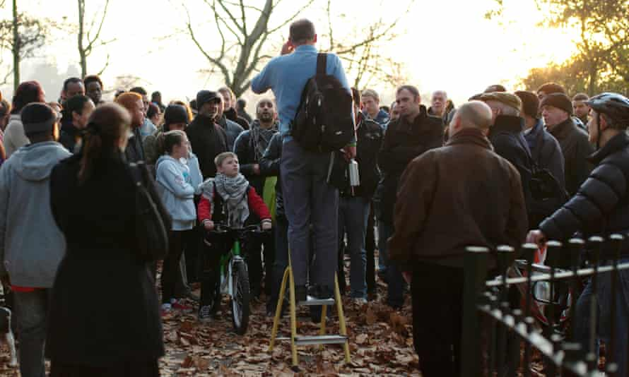 People gather around to listen to a man at Speakers' Corner in Hyde Park, London
