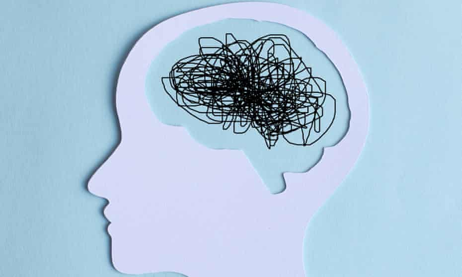 Paper cut out of a human head with a chaotic line drawing for a brain
