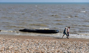 People walk past a waterlogged, discarded boat, washed up on a beach in Lydd on Sea, near to where people have been arriving in southeast England