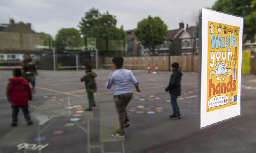 Children maintain physical distancing while playing in the playground at Earlham primary school in London