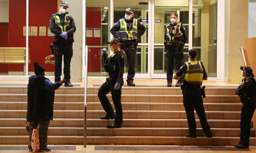 Five police stand outside the glass doors of a Melbourne public housing estate