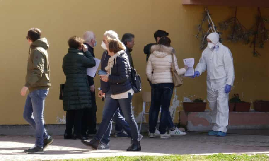 People line up to undergo a voluntary test for coronavirus in Vò, Italy, 8 March 2020.