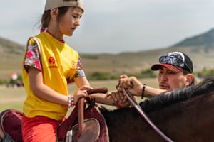 Ellana, eight, is coached by her father, Kostumov Farhat, on how to hold the reins to control her horse