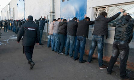Russian police detain migrant workers during a raid at a vegetable warehouse complex in Moscow.