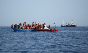 The rescue ship Alan Kurdi picking up 44 people from a wooden boat in the Mediterranean