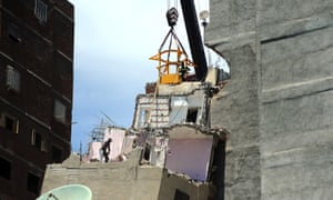 Work begins to demolish the leaning building.