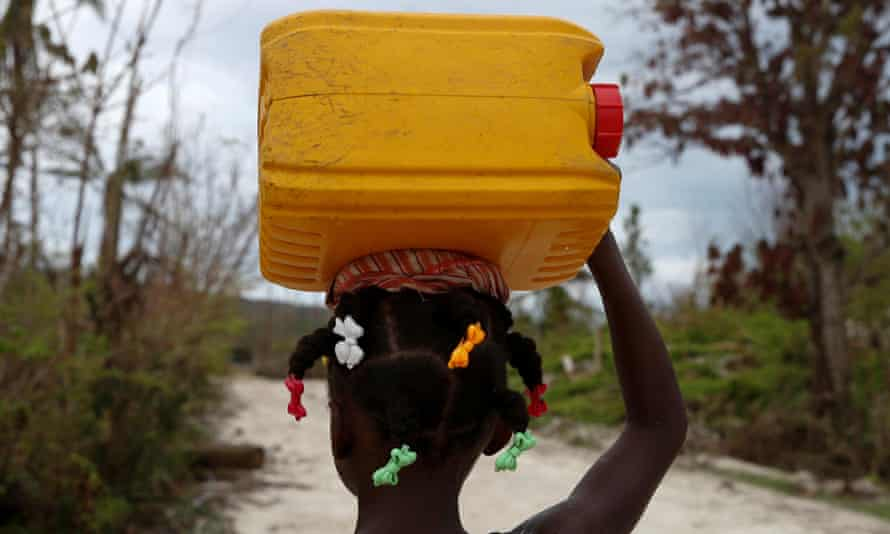 A girls carries a plastic container filled with water in Jeremie, Haiti