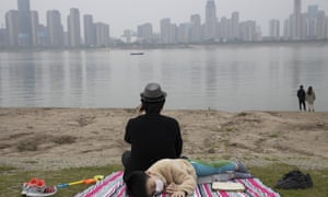 In this April 16, 2020, photo, a child wearing a mask against the coronavirus rests on the banks of the Yangtze River in Wuhan in central China's Hubei province.