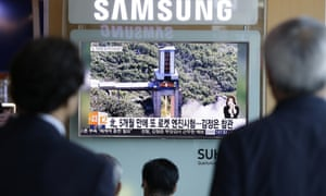 People watch a TV news showing an image that North Korea's Rodong Sinmun newspaper reports of the ground test of a high-powered engine of a carrier rocket at the country's Sohae Space Centre in Seoul, South Korea.