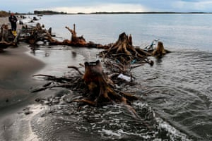 A man fishes from a shore washed with tree trunks and roots, in Kune, Lezhe, Albania