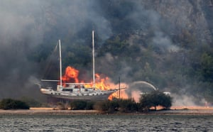 Firefighters battle to extinguish flames next to a boat in the Milas district of Mugla, Turkey