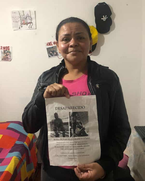 Dolores Barros holds a missing sign showing her son, Duvan Barros.