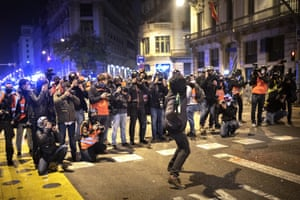 People take photos of a man throwing a bottle during clashes in Barcelona