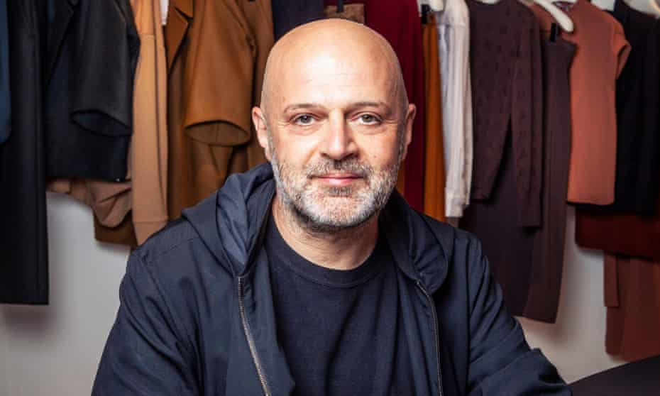 Hussein Chalayan in front of a rail of his designs