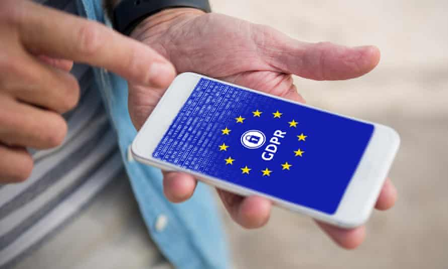 Person holding a mobile phone with a locked screen stating GDPR with a background of the logo for the EU