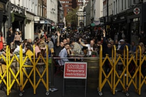People react to being photographed as they sit outside on a street closed to traffic, so bars and restaurants can continue to stay open, in the Soho area of central London, on Saturday, 19 September 2020. Fresh nationwide lockdown restrictions in England appear to be on the cards soon as the British government targeted more areas Friday in an attempt to suppress a sharp spike in new coronavirus infections.
