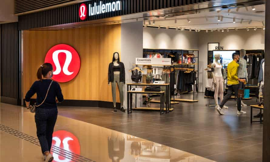 A shopper walks past the Canadian sportswear clothing band, Lululemon logo and store seen in Hong Kong.