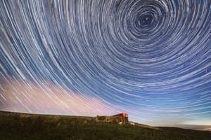 A digital composite of 233 photographs taken over a period of an hour and 57 minutes. It shows star-trails around the north celestial pole with a couple of meteor streaks to the right of the frame.