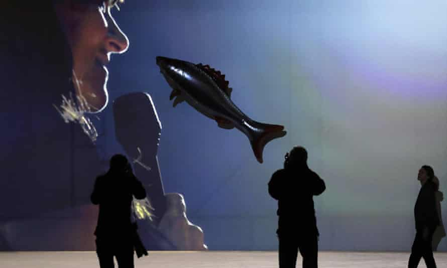 A balloon fish suspended in front of a screen, part of Philippe Parreno's Anywhen.