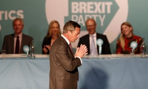 Nigel Farage standing in front of a line of people sitting down