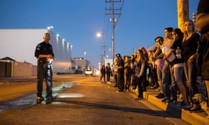 Corporal Anthony Encinas of the Vernon Police Department tells protestors to stay on the sidewalk until the next truck bearing pigs arrives.