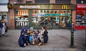 A group of women and a child eat in Oldham high street, 2016. Oldham town centre