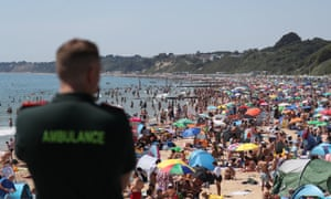 A member of the ambulance service looks out from Bournemouth pier as crowds gathered on the beach yesterday.