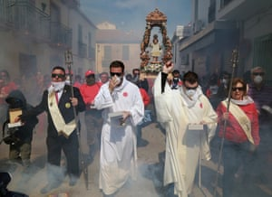 Smoke billows around a group of people in long robes and old-fashioned suits at the front of a procession