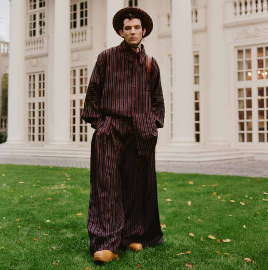 Actor Josh O'Connor standing outside stately home