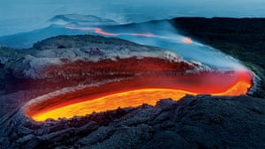 Winner - Earth's Environments: Etna's river of fire by Luciano Gaudenzio. From a great gash on the southern flank of Mount Etna, lava flows within a huge lava tunnel, re-emerging further down the slope as an incandescent red river, veiled in volcanic gases. Luciano described the vent as resembling 'an open wound on the rough and wrinkled skin of a huge dinosaur'.
