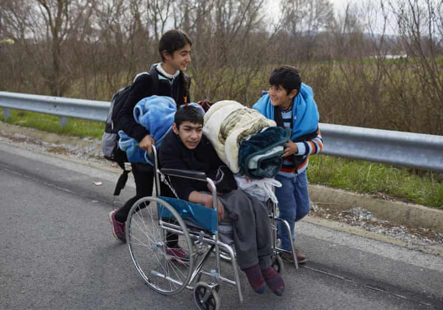 Children push a boy in a wheelchair along a road towards a refugee camp near the Greece-Macdonia border.