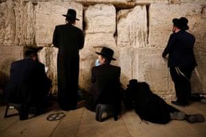 Jewish worshippers pray on Tisha B'Av at the Western Wall in Jerusalem, Israel