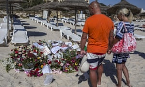 Tourists pay their respects at a makeshift memorial in Tunisia to victims of the 2015 terror attack