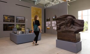 A visitor walks past a bust at the Wende Museum.